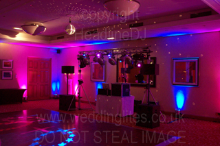 wedding dj equipment ready to be used with led uplighting along the back wall with pink and blue colour washing the wall and ceiling